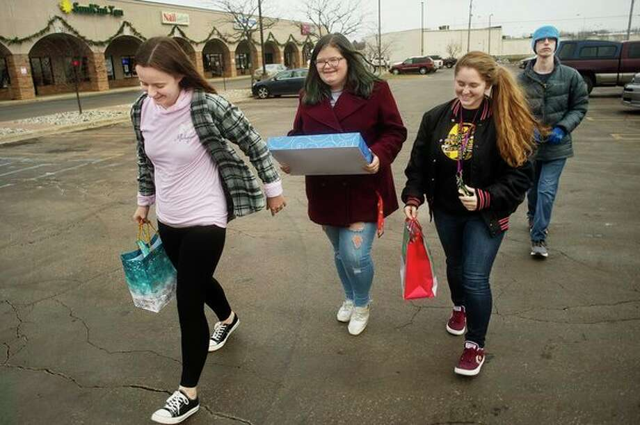 From left, Morgan Simons, 17, Mattie Davis, 18, Allie Woollard, 17, all Girl Scouts with Troop 50328, and Justin Dyer, 18, carry gifts the troop is donating to local foster kids into the Midland Department of Health and Human Services offices on Tuesday in Midland. (Katy Kildee/kkildee@mdn.net)