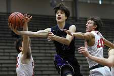 Avery Eugster of St. Mary's Hall penetrates and shoots as Robbie Hilliard, left, and Trevor Allison, right, of Corpus Christi Ray defend during the San Antonio Independent School District boys basketball tournament at the Alamo Convocation Center on Friday, Dec. 7, 2018. St. Mary's Hall won, 76-73.