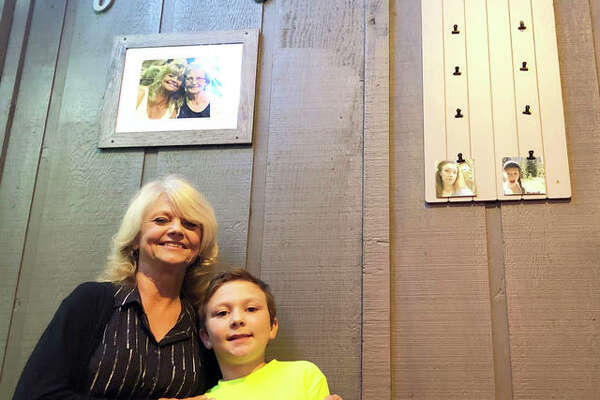 The Back Bar owner Marion Gilson stands with her grandson, Zach, at the business's soft opening earlier this month. The business is located at 228 N. Main St. Gilson's mother died two years ago, pictured in the framed photo, and believes she has continuously motivated her through all the ups and downs of opening a business.