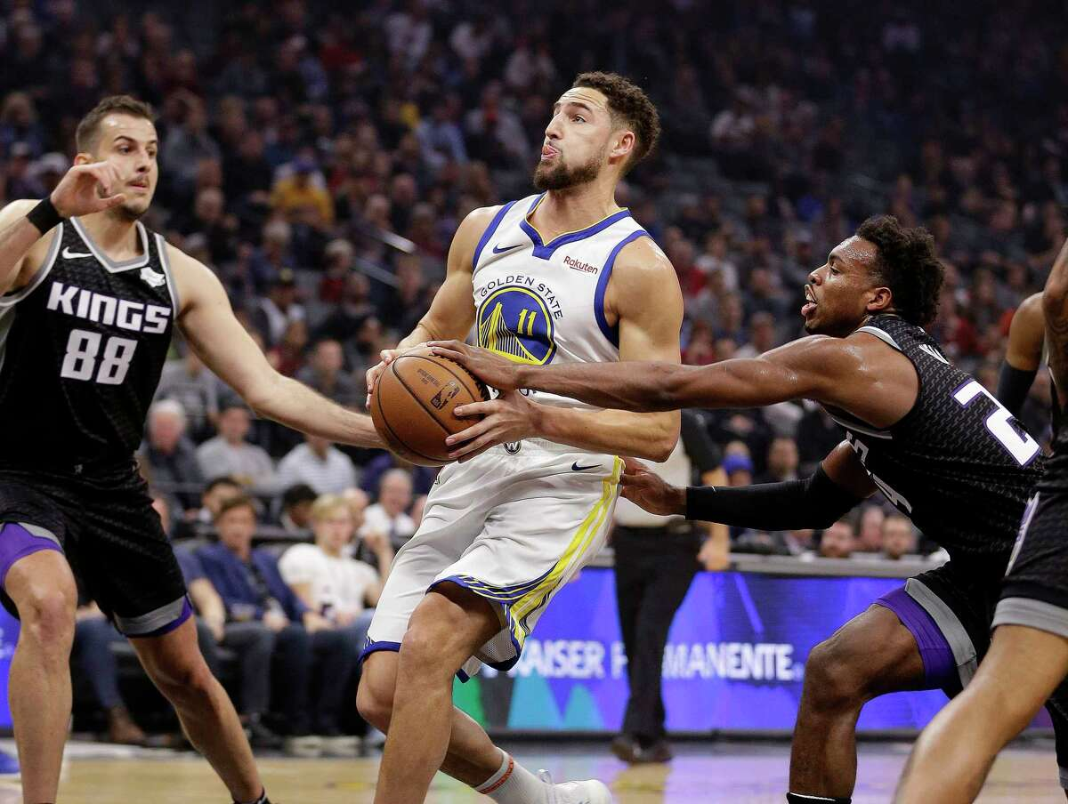 Golden State Warriors guard Klay Thompson, center, drives to the basket between Sacramento Kings' Nemanja Bjelica, left, and Buddy Hield, right, during the first half of an NBA basketball game Friday, Dec. 14, 2018, in Sacramento, Calif.