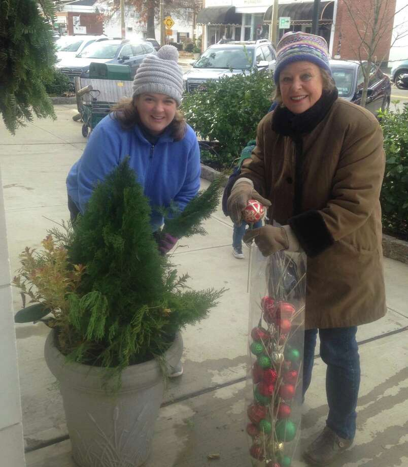 Old Greenwich Garden Club members Wendy Yu and Mary Bishop were among the many club volunteers who recently went out onto Sound Beach Avenue in Old Greenwich to decorate the main business district of the village with festive holiday touches, continuing a tradition in town. Photo: Contributed Photo