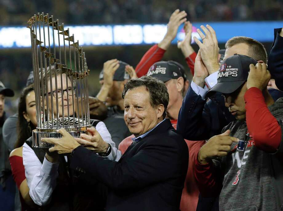File- This Oct. 28, 2018, shows Boston Red Sox owner John Henry, partially hidden at left, and chairman Tom Werner holding the championship trophy beside manager Alex Cora, right, after Game 5 of baseball's World Series against the Los Angeles Dodgers in Los Angeles. The World Series champion Red Sox owe $11.95 million in luxury tax for having baseball's top payroll, according to final calculations by the commissioner's office obtained by The Associated Press. The only other team that owes is the Washington Nationals, who must pay $2.39 million. Photo: David J. Phillip, AP / Copyright 2018 The Associated Press. All rights reserved