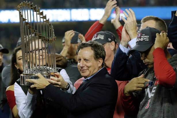 File- This Oct. 28, 2018, shows Boston Red Sox owner John Henry, partially hidden at left, and chairman Tom Werner holding the championship trophy beside manager Alex Cora, right, after Game 5 of baseball's World Series against the Los Angeles Dodgers in Los Angeles. The World Series champion Red Sox owe $11.95 million in luxury tax for having baseball's top payroll, according to final calculations by the commissioner's office obtained by The Associated Press. The only other team that owes is the Washington Nationals, who must pay $2.39 million.