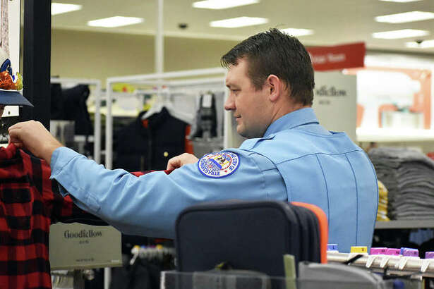 """Edwardsville Police Officer Jason Bearden helps his shopper in the clothing department at Target during the annual """"Christmas with a Cop"""" event on Saturday."""