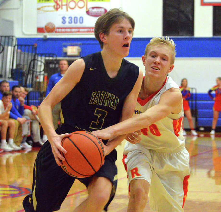 Father McGivney's Kellen Weir (left) drives past Roxana's Cade Slayden during Friday's game at Milazzo Gym in Roxana. Photo: Scott Marion / Hearst Illinois