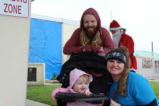A family at the second annual Santa Run hosted by CASA at the Jack Brooks Regional Airport.