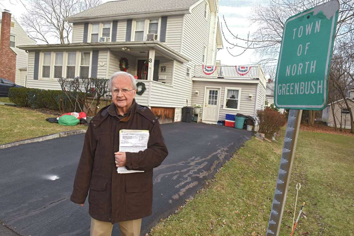 Kenneth Downes stands on the Town of North Greenbush side of his property on Tuesday, Dec. 11, 2018 in Rensselaer, N.Y. The white dot on his driveway is an indication of where the sign at right should be. His house to the left of the white dot is on the City of Rensselaer side. He is being taxed by the town of North Greenbush even though he's a city of Rensselaer resident. (Lori Van Buren/Times Union)