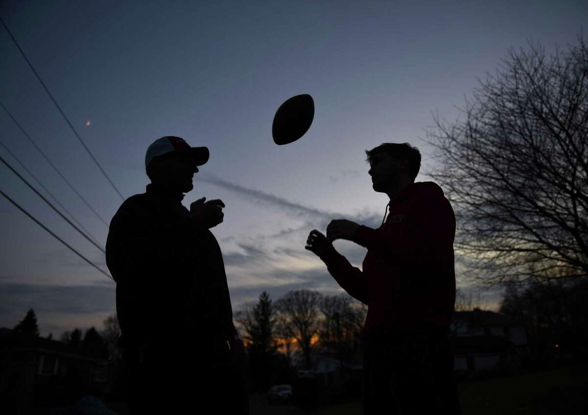 Larry DeLuca, left, tosses a football to his son, L.J. DeLuca, at their home in the Cos Cob section of Greenwich, Conn. Wednesday, Dec. 12, 2018. L.J. played linebacker on Greenwich High School's 2018 undefeated team and his father Larry played defensive end on the 1983 undefeated team. Despite an undefeated record, Larry's 1983 squad finished ranked No. 3 in the state, while L.J.'s team was ranked first, and Larry admits that he thinks his son's team is better.