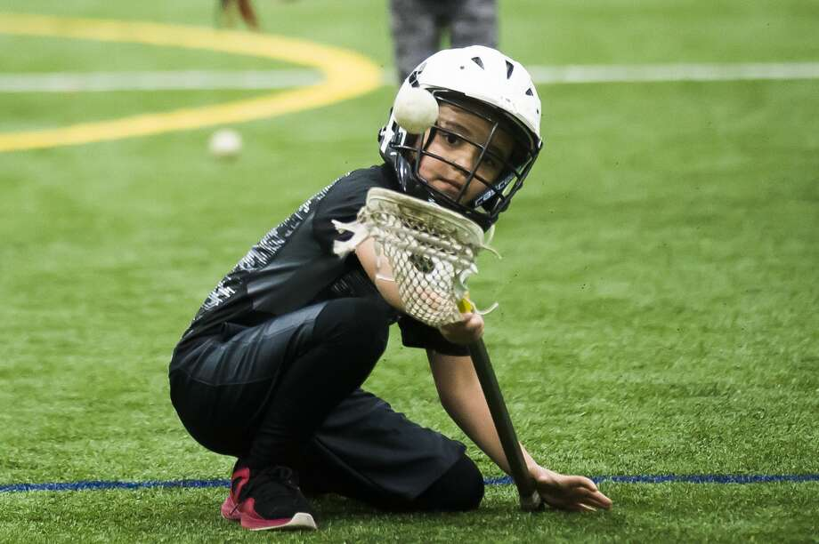 "Josiah Vajcner of Midland, 7, practices scooping the ball during a ""Try Lacrosse Free"" event hosted by the Midland Lacrosse Club on Saturday, Dec. 15, 2018 at Midland Civic Arena. (Katy Kildee/kkildee@mdn.net) Photo: (Katy Kildee/kkildee@mdn.net)"