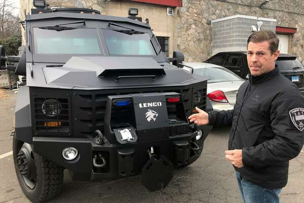 Lt. Chris Baker, the commander of the Stamford police's SWAT unit, pointing out details of the department's new $230,000 BearCat armored personnel carrier.