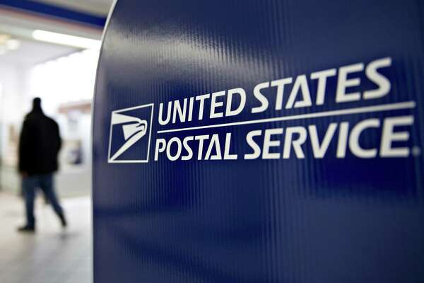 Signage is seen at the United States Postal Service (USPS) Joseph Curseen Jr. and Thomas Morris Jr. post office station in Washington, D.C., U.S., on Tuesday, Dec. 12, 2017. The USPS said it expects to deliver over 15 billion total pieces of mail this holiday season with expanded Sunday delivery operations in certain areas, delivering over six million packages each Sunday in December. Photographer: Andrew Harrer/Bloomberg ORG XMIT: 775090767