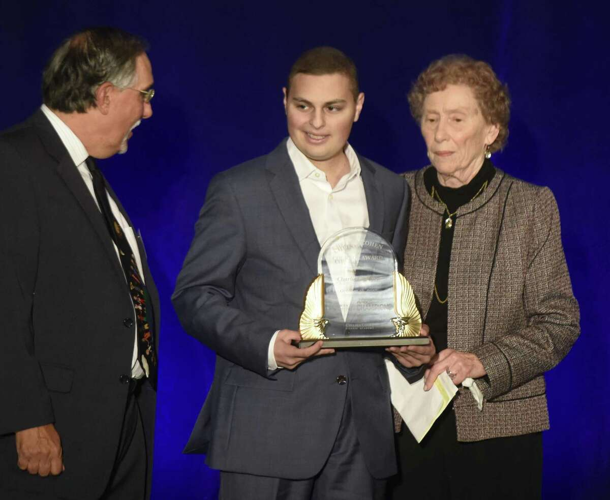 Fairfield Ludlowe graduate Charlie Capalbo, center, accepts the Chelsea Cohen Courage Award from Fairfield County Sports Commission executive director Tom Chiappetta and Cohen's mother, Barbara Rittner, at the Fairfield County Sports Commission Hall of Fame induction ceremony Oct. 16, 2017.