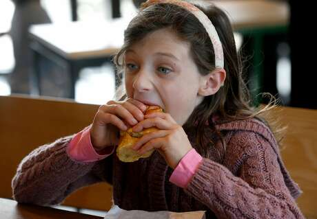 Elsa Wick, 7, bites into a Shack Burger after the first Shake Shack restaurant in Northern California opens at the Stanford Shopping Center in Palo Alto, Calif. on Saturday, Dec. 15, 2018.