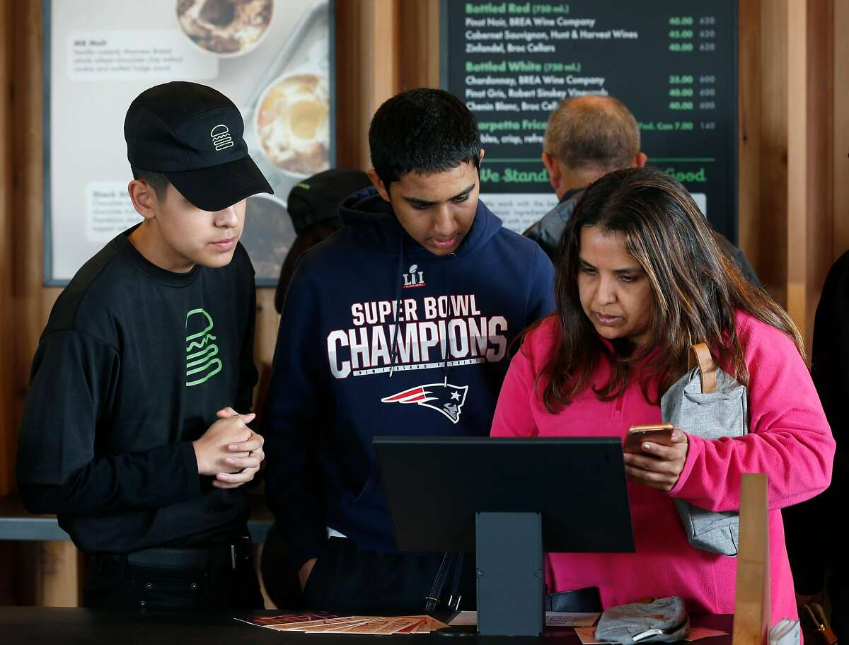 Employee Justin Ramirez (left) helps Nikash Bhardwaj and his mother Aparna Bhardwaj place their order after the first Shake Shack restaurant in Northern California opens at the Stanford Shopping Center in Palo Alto, Calif. on Saturday, Dec. 15, 2018.