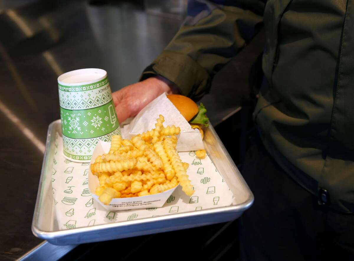 Ronald Miller carries away the first burger off the grill and the first fries out of the fryer after the first Shake Shack restaurant in Northern California opens at the Stanford Shopping Center in Palo Alto, Calif. on Saturday, Dec. 15, 2018.