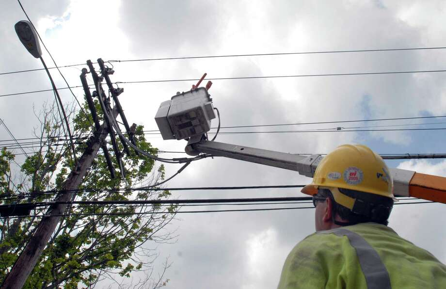 United Illuminating workers Fritz Bonyai (right) and Marilyn Nilsen-Jerz work on the powerlines on Jones Hill Rd in West Haven, Friday afternoon. Caroline Kowalczyk/The Register 06.10.11