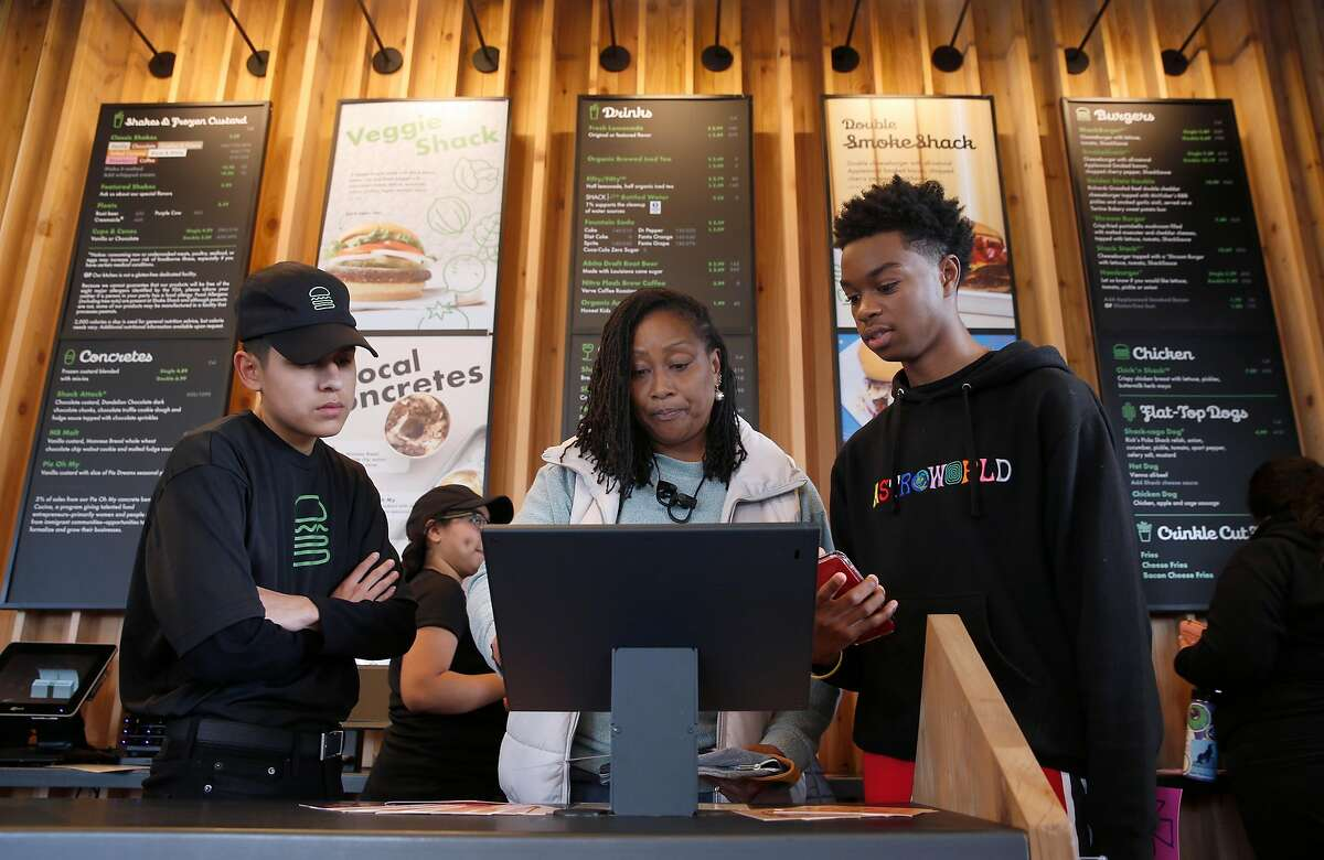 Employee Justin Ramirez (left) helps Anna Hodges and her son Tiere place their order after the first Shake Shack restaurant in Northern California opens at the Stanford Shopping Center in Palo Alto, Calif. on Saturday, Dec. 15, 2018.