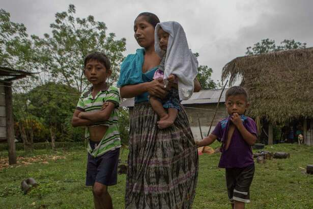 Claudia Maquin, 27, walks with her three children, Abdel Johnatan Domingo Caal Maquin, 9, left, Angela Surely Mariela Caal Maquin, 6 months, middle, and Elvis Radamel Aquiles Caal Maquin, 5, right, as they leave Domingo Caal Chub's house, Claudia's father in law, in Raxruha, Guatemala, Saturday, Dec. 15, 2018. Claudia Maquin's daughter, 7-year-old Jakelin Amei Rosmery Caal, died in a Texas hospital, two days after being taken into custody by border patrol agents in a remote stretch of New Mexico desert.