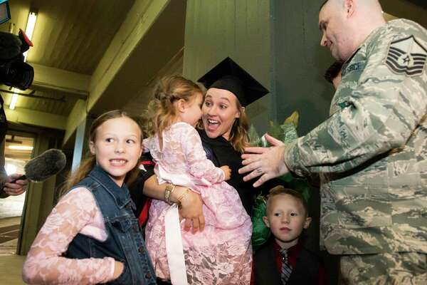 Heather Jo McNeil, center, holds her daughter Regan, 2, as she and her children Lia, 8, and Joel,6, react after Master Sgt. Nathan McNeil, made a surprise appearance as she walked the stage to receive her Bachelor's of Science degree from the University of the Incarnated Word at Freeman Coliseum on Saturday, December 15, 2018 in San Antonio. He's been deployed for 13 months, and Heather and her family didn't know that he was back.