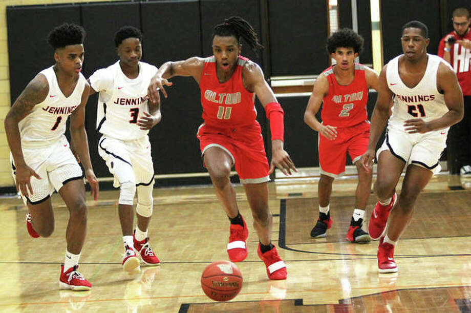 Alton's Donovan Clay (11) heads upcourt on the break ahead of Jennings' Donnel Carter (1), Trevon Lane (3) and Vernell Sims (right) while the Redbirds' Drew Jones trails the play Saturday afternoon at the Ramey Shootout in Webster Groves, Missouri. Photo: Greg Shashack / The Telegraph