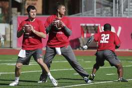 Quarterbacks Dustin Vaughan (center) and Logan Woodside drop back for passes as the San Antonio Commanders hold mini-camp at UIW Tom Benson Football Stadium on Thursday, Dec. 13, 2018.