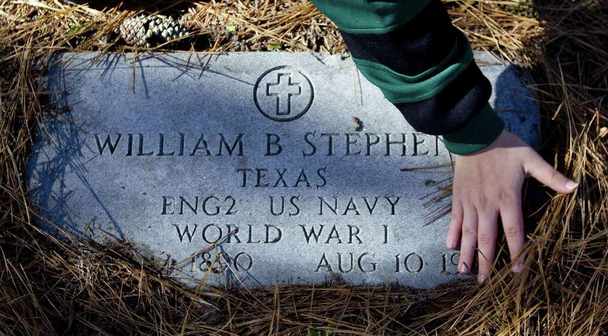 Hope Flores uncovers the grave of World War I veteran William Stephen as members of the Willis community along with American Legion Post 618 take part in the annual laying of Christmas wreaths at the graves of veterans, Saturday, Dec. 15, 2018, in Willis.