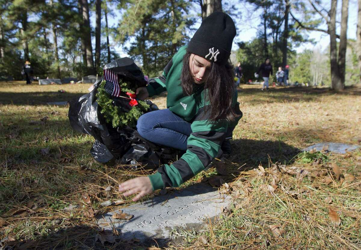 Hope Flores uncovers the grave of Army veteran Hoyt Garrison before adorning it with a Christmas wreath as members of the Willis community along with American Legion Post 618 took part in the annual laying of Christmas wreaths at the graves of veterans, Saturday, Dec. 15, 2018, in Willis.