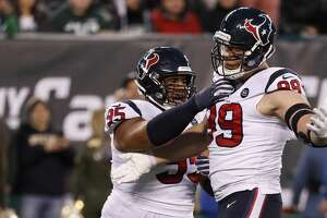 Houston Texans defensive ends Christian Covington (95) and J.J. Watt (99) celebrate after Watt sacked New York Jets quarterback Sam Darnold during the first quarter of an NFL football game at MetLife Stadium on Saturday, Dec. 15, 2018, in East Rutherford, N.J.