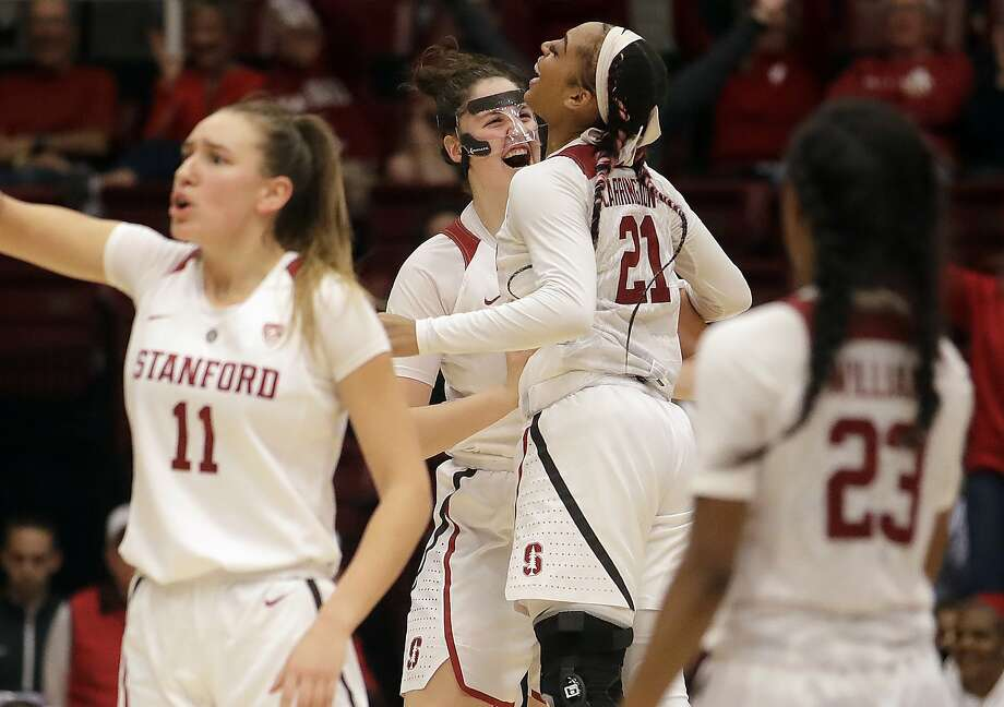 Stanford center Shannon Coffee (center left) and guard Dijonai Carrington (21) celebrate in the second half. Photo: Jeff Chiu / Associated Press