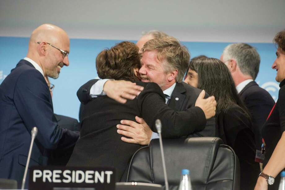 Dignitaries embrace at the United Nations Climate Change Conference in Katowice, Poland, Dec. 15, 2018. Diplomats from nearly 200 countries reached a deal on Saturday to keep the Paris climate agreement alive by adopting a detailed set of rules to implement the pact. (Karolina Jonderko/The New York Times) Photo: KAROLINA JONDERKO / NYTNS