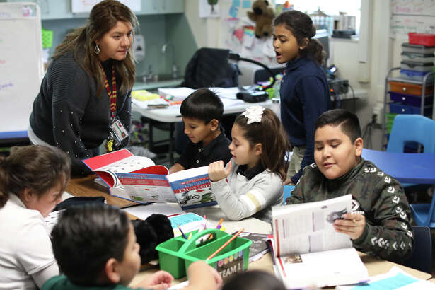Third graders in Kristine Gonzalez's class at South Elementary look over dictionaries donated by the Midland West Rotary club, Dec. 5, 2018. The Midland West Rotary club gives every third grader in Midland Independent School District a dictionary each year as an annual service project. James Durbin/Reporter-Telegram