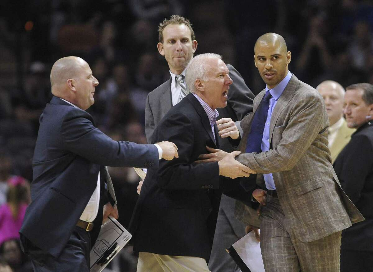 San Antonio Spurs coach Gregg Popovich, middle, is held back by assistant coaches Jim Boylen, left, Sean Marks, top, and Ime Udoka as he argues with officials during second-half NBA action against Portland in the AT&T Center on Friday, Jan. 17, 2014. The Trailblazers won, 109-100.