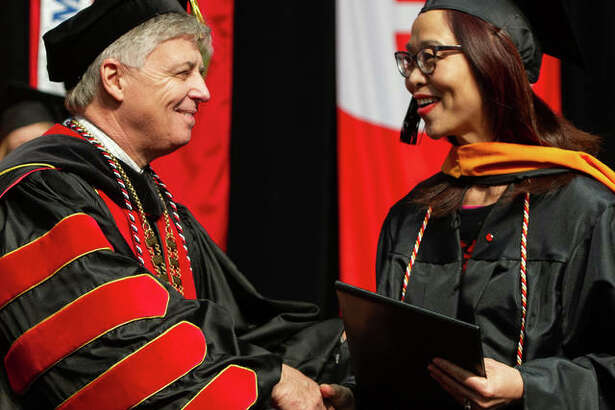 Southern Illinois University Edwardsville Chancellor Randy Pembrook, Ph.D., left, shakes the hand of a newly eligible graduate during the 2018 Fall Commencement exercises, which were Friday and Saturday in the Vadalabene Center at SIUE.