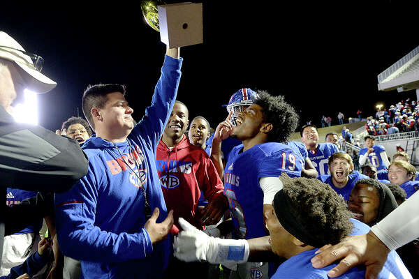 West Brook's Bruins celebrate as coach Eric Peevey raises their trophy after defeating Austin Westlake 35 - 30 in the Class 6A state semifinals at Legacy Stadium. Photo taken Saturday, December 15, 2018 Kim Brent/The Enterprise