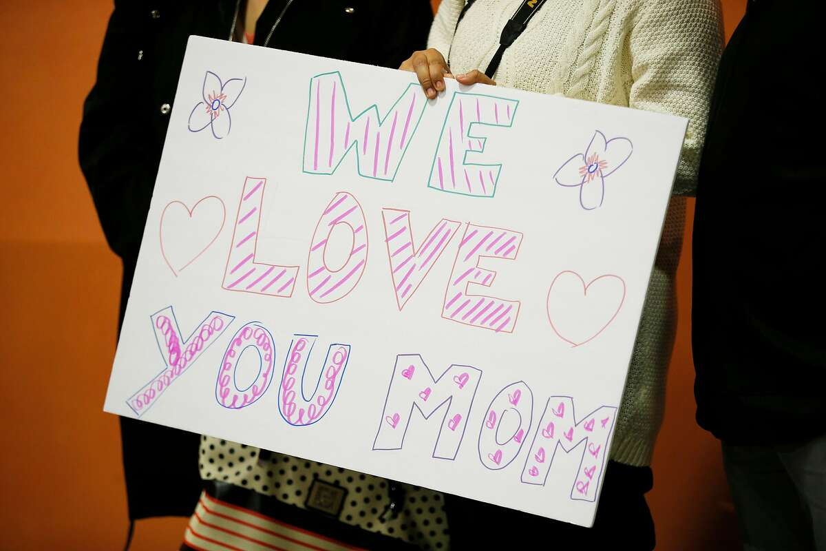 Melin Sanchez holds a sign she brought to welcome her mother Maria Mendoza-Sanchez at SFO on Saturday, Dec. 15, 2018, in San Francisco, Calif. Mendoza-Sanchez, a nurse who was separated from her children and deported to Mexico last year after more than two decades in Oakland, won her improbable fight to return to the United States. Her visa was approved by U.S. Citizenship and Immigration Services.