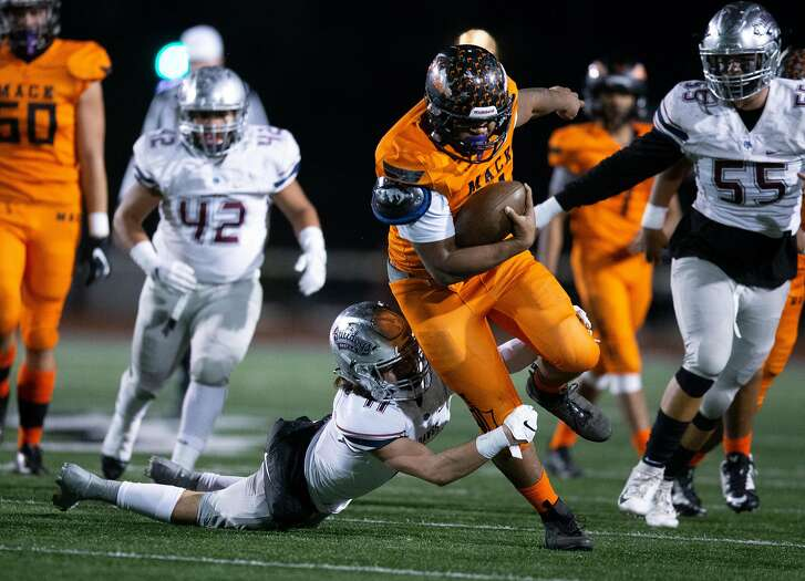 McClymonds running back Jarmar Julien (4) breaks the tackle of Garfield defender Bruce Gonzalez (11) in the first quarter of a CIF Section 4A state high school football championship game, on Saturday, Dec. 15, 2018 in Oakland, Calif.