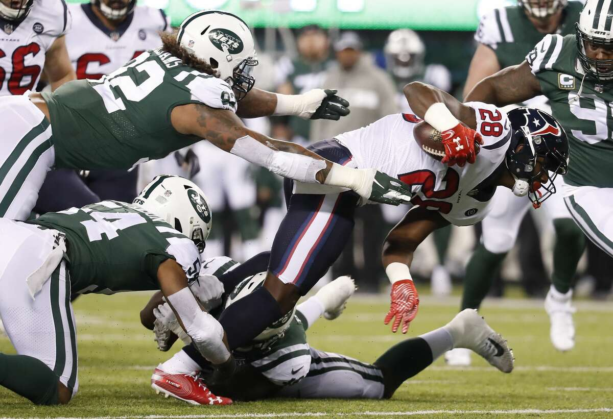 Houston Texans running back Alfred Blue (28) is tripped up by New York Jets inside linebacker Avery Williamson (54) during the second quarter of an NFL football game at MetLife Stadium on Saturday, Dec. 15, 2018, in East Rutherford, N.J.