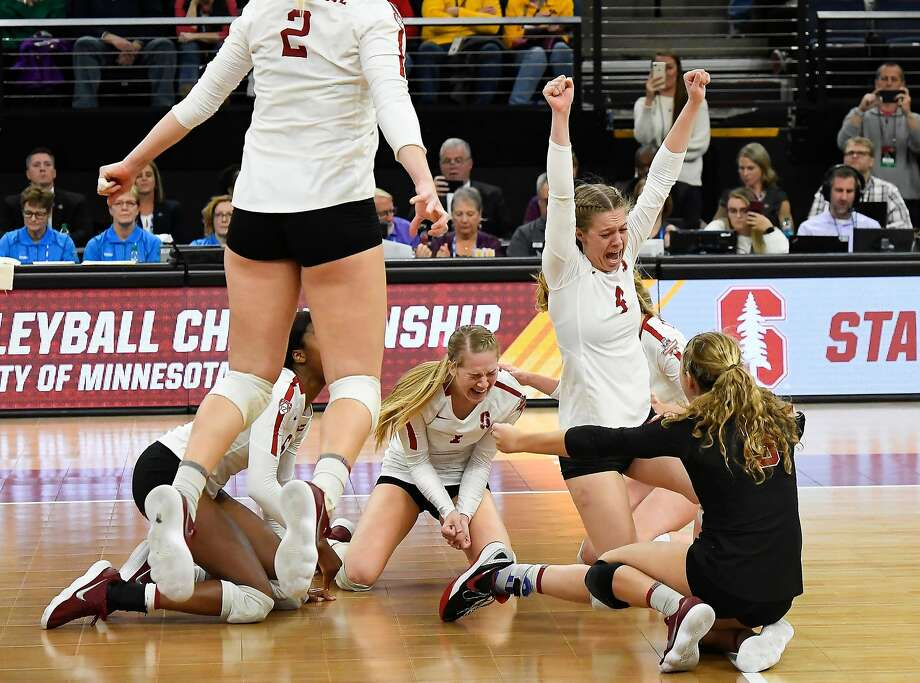 Meghan McClure (right), Jenna Gray (middle) and the Stanford volleyball team celebrate after defeating Nebraska in five sets on Saturday night for a record eighth national title. Photo: Aaron Lavinsky / Minneapolis Star Tribune