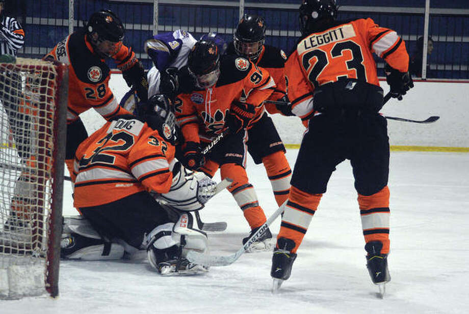 Edwardsville goalie Mason Young, second from left, tries to control to the puck as four teammates come to his aid during the first period of Saturday's game against CBC at the Affton Ice Rink. Photo: Scott Marion/Intelligencer