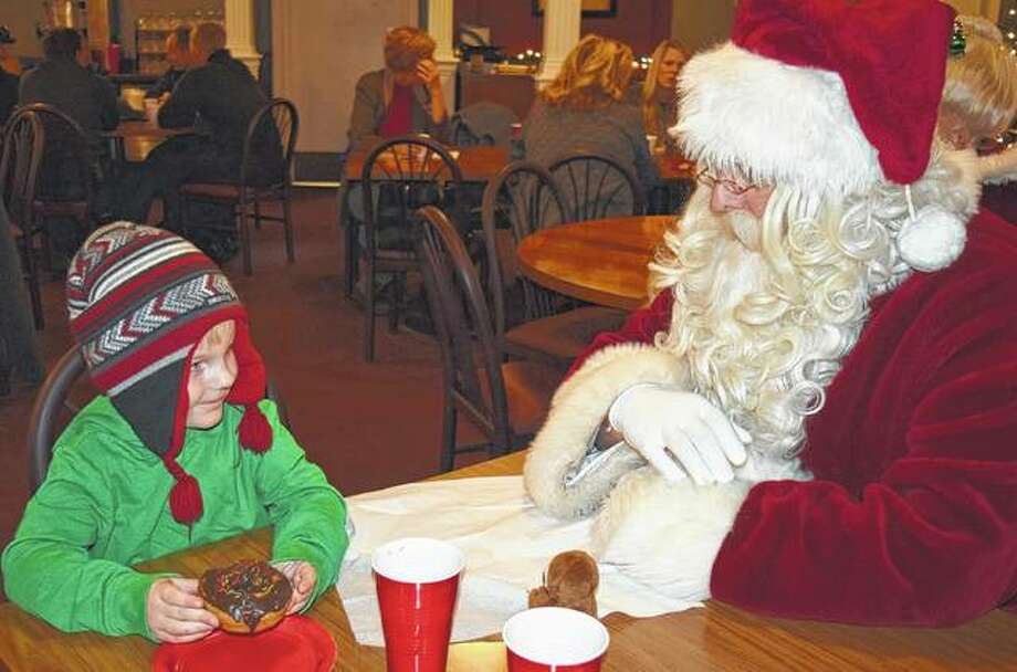 Trent Orris, 4, the son of Erika and Marc Orris of Jacksonville, eats a donut while talking with Santa on Saturday at the Elks Lodge during the Heart of Jacksonville's Breakfast with Santa. Photo: Samantha McDaniel-Ogletree | Journal-Courier