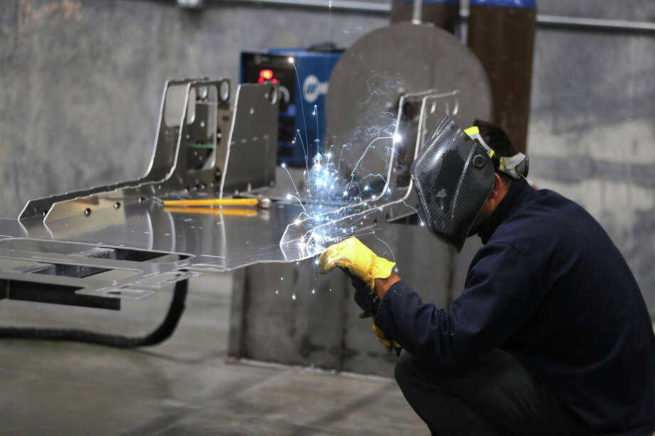 A worker welds a custom built aluminum body frame for a Venice roadster model vehicle at the Vanderhall Motor Works manufacturing facility in Provo, Utah. Photo: Bloomberg Photo By George Frey. / © 2018 Bloomberg Finance LP