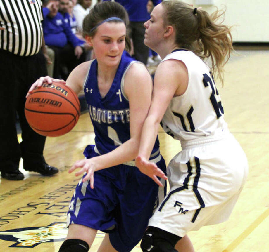 Marquette Catholic's Abby Williams (left), shown driving on Father McGivney's Mariah Starnes in a victory Thursday night in Glen Carbon, scored 10 points Saturday in an overtime loss at Freeburg. Photo: Greg Shashack / The Telegraph