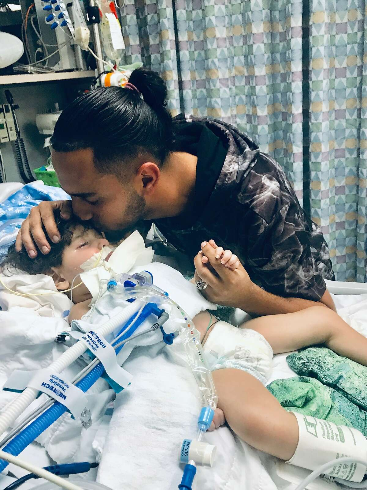 Ali Hassan, of Stockton, kisses his 2-year-old son Abdullah at UCSF Benioff Children's Hospital in Oakland. The child is on life support while his Yemeni mother Shaima Swileh is stuck in Egypt, unable to enter the U.S. because of the Trump administration's so-called Muslim ban.