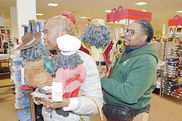 Krista and Markell Parks of St. Louis wait in line to purchase items on Saturday at JCPenney in the Alton Square Mall.