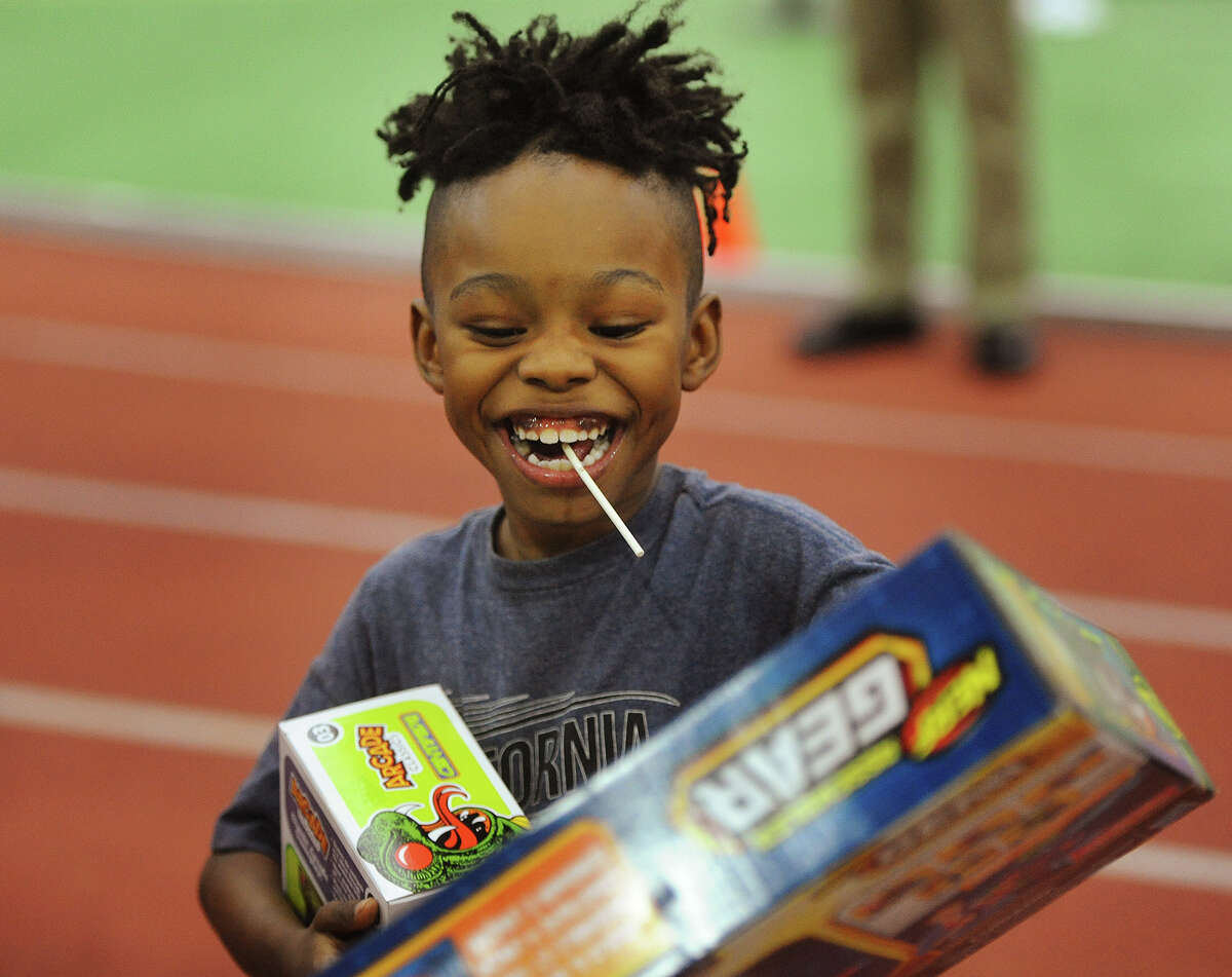 Ronnie Bellgreen, III, 7, of New Haven, breaks into a big smile as he receives toys at the 5th Annual Winter Wonderland holiday toy giveaway at the Floyd Little Fieldhouse in New Haven, Conn. on Sunday, December 16, 2018.