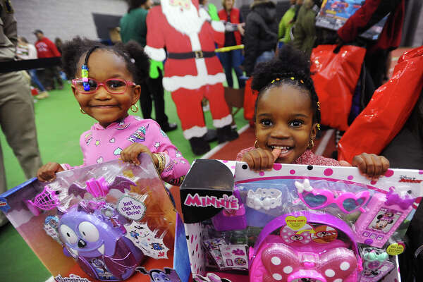 R-Mani Johnson, 3, left, and Aloni Harmon, 2, of New Haven, with their toys at the 5th Annual Winter Wonderland holiday toy giveaway at the Floyd Little Fieldhouse in New Haven, Conn. on Sunday, December 16, 2018.