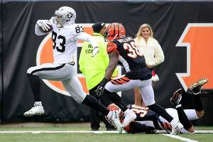 CINCINNATI, OH - DECEMBER 16:  Darren Waller #83 of the Oakland Raiders breaks a tackle by Jessie Bates #30 of the Cincinnati Bengals before being dragged down short of the goal line by Shawn Williams #36 during the second quarter at Paul Brown Stadium on December 16, 2018 in Cincinnati, Ohio. (Photo by Andy Lyons/Getty Images)