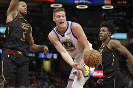 Golden State Warriors' Jonas Jerebko (21), from Sweden, passes the ball between Cleveland Cavaliers' Rodney Hood (1) and Cleveland Cavaliers' Collin Sexton (2) in the second half of an NBA basketball game, Wednesday, Dec. 5, 2018, in Cleveland. The Warriors won 129-105. (AP Photo/Tony Dejak)