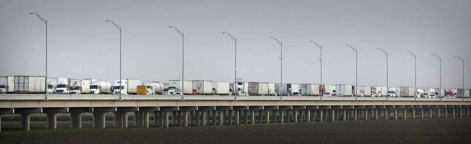A long line of trucks wait on the Pharr-Reynosa International Bridge to enter the United States as others make their way into Mexico. Photo: Photos By Bob Owen / Staff Photographer / ©2018 San Antonio Express-News