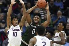 Manhattan's Warren Williams (0) looks to pass as UConn's Brendan Adams (10), and Christian Vital defend on Saturday.